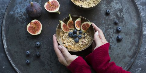 woman's hands holding bowl of porridge with sliced figs, blueberries and dried berries