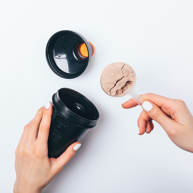 woman's hands putting scoop of chocolate protein