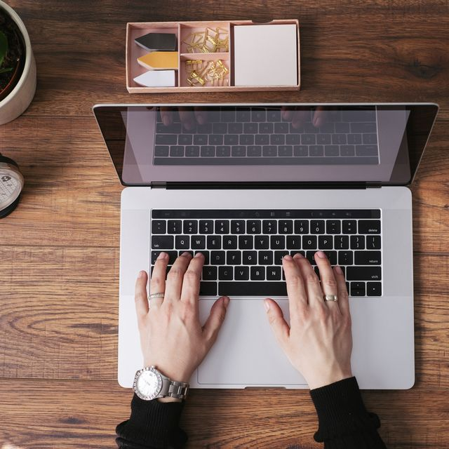 Woman's hands working on laptop at home office, top view