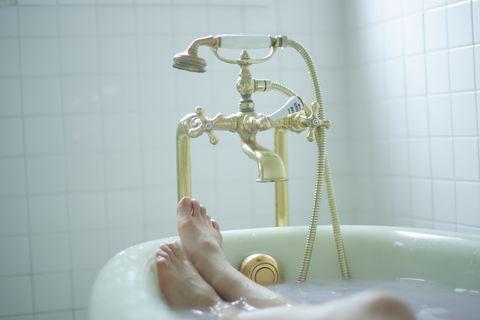 woman's legs in bathtub