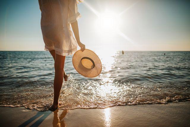 een vrouw spettert met haar voeten in het water op het strand