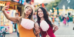 Women at the amusement park eating pink cotton candy and taking selfie/vlogging