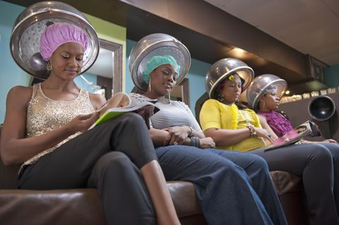 women friends sitting under hair dryers at salon