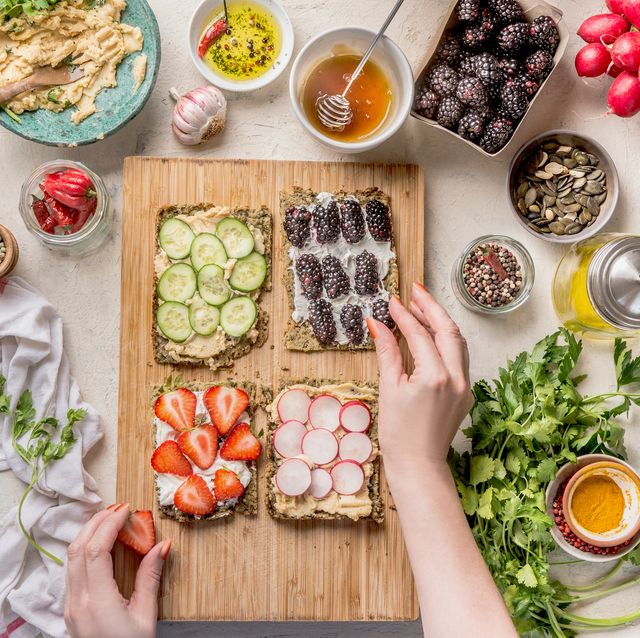 women hands making sandwiches with green healthy gluten free chips bread oder falafel bread with fresh herbs, chickpeas hummus , nuts and olive oil , berries and vegetables on white kitchen table with ingredients