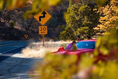 Women road trip driving red car in California autumn road.