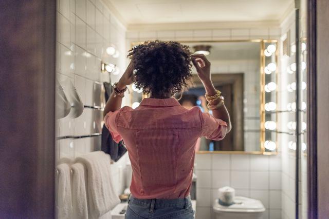Woman preparing hair in bathroom