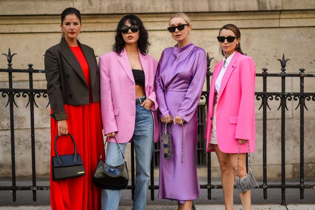 paris, france   july 07 l r gili biegun wears gold fendi earrings, gold earrings, a red long flowing dress, gray short blazer jacket, a black shiny leather chiquito handbag from jacquemus, gold bracelet,  xiayan wears black sunglasses, silver earrings, a black headband t shirt, a pale pink oversized blazer jacket, a black grained leather belt, blue faded denim jeans ripped flared pants, rings, a black shiny leather prada handbag,  justyna czerniak wears black sunglasses, gold earrings, a shiny purple turtleneck long sleeves flowing long dress, silver yoke handbag,  julia comil wears black sunglasses, a rhinestone pendant earring, gold earrings, a white shirt, a pink oversized blazer jacket, a gray leather crocodile pattern belt, white suit shorts, silver nailed  studded handbag, outside zuhair murad, during paris fashion week   haute couture fallwinter 20212022, on july 07, 2021 in paris, france photo by edward berthelotgetty images