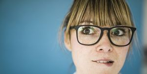 Portrait of woman with glasses biting on her lip