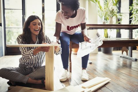 Women with instructions assembling furniture
