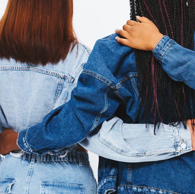 3 women in denim jackets with hands around each other
