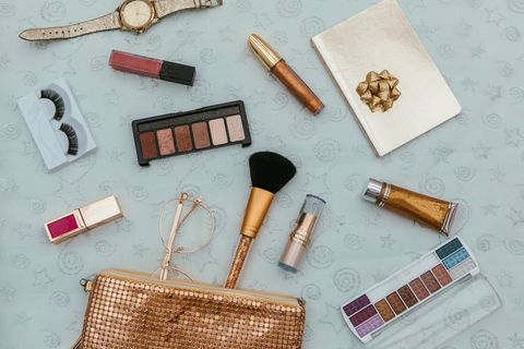 Women's fashion.  handbag, makeup brushes on golden background. magazines, social media. Top view. Flat lay.
