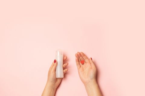Womens hands hold intimate grease and a red heart shape on a pink background