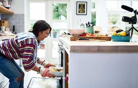 Vrouw haalt schaal uit de oven