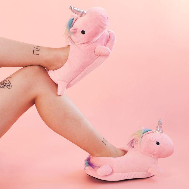woman in furry coat wearing unicorn slippers
