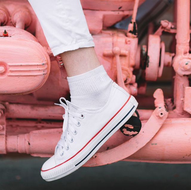 woman in white sneakers on pink painted motorcycle