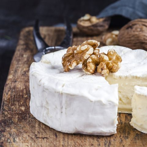 wooden board with sliced camembert, walnuts and grapes