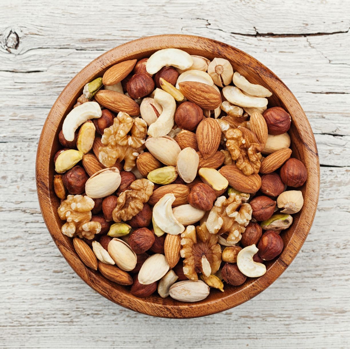 Wooden bowl with nuts. Walnut, pistachios, almonds, hazelnuts. Flat lay.