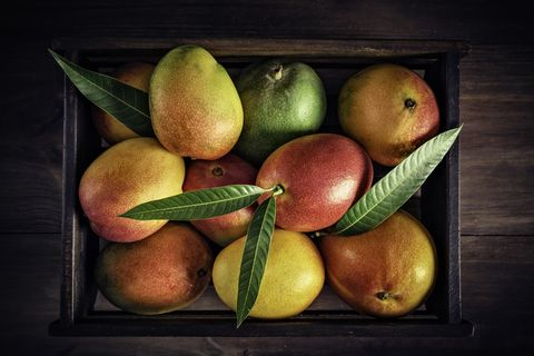 tropical fruits wooden crate with assorted mangos in rustic kitchen natural lighting