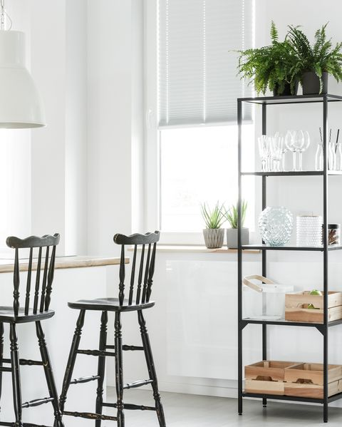 Wooden crates and fern on shelf in white dining room with black bar stools at kitchen island