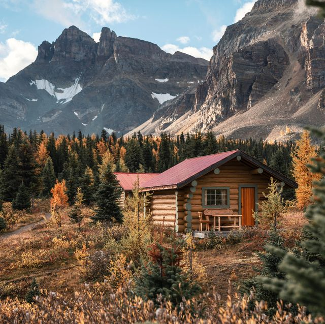 wooden huts with rocky mountains in autumn forest at assiniboine provincial park