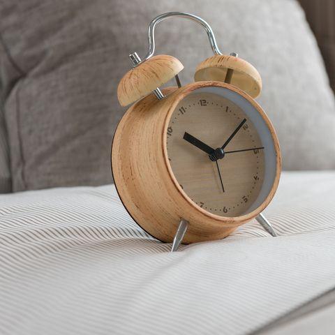 wooden modern alarm clock on bed