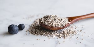 Wooden spoon with chia seeds and blueberries on marble counter