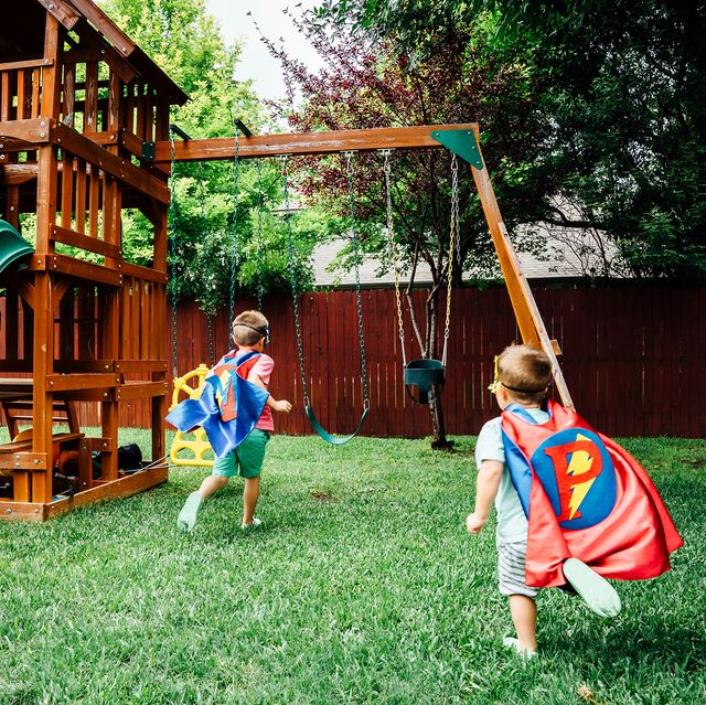 kids in superhero capes playing with wooden swing set