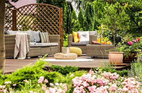 Wooden terrace with couch with pillows, armchair, table with fresh fruits and candles on wicker footrest