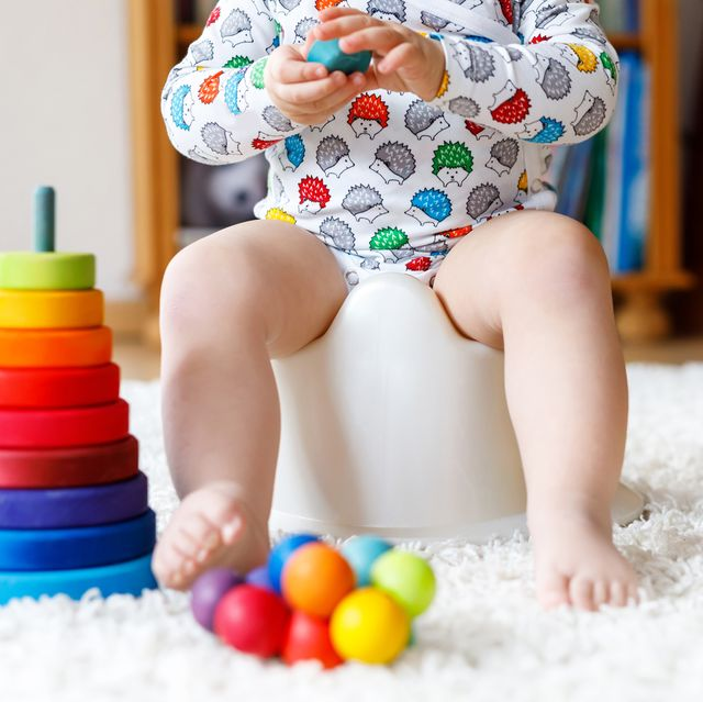 kid playing with rainbow wooden toys
