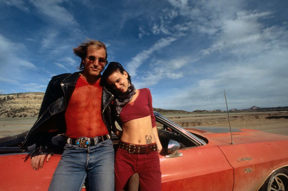 Natural Born Killers (1994) Woody Harrelson and Lewis pose in front of a car before filming a scene for Natural Born Killers. The two play a couple who become mass murderers and are glorified by the media.
