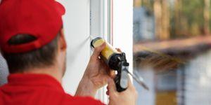 worker applying caulk around window frame