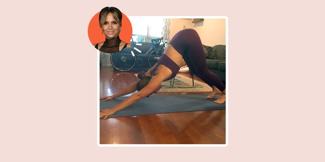 writer performing downward facing dog yoga pose at home like halle berry