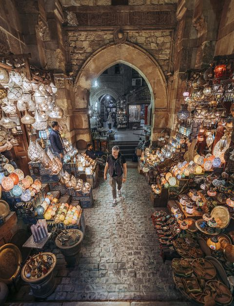 a man walks through a shopping bazaar in cairo egypt and is surrounded by colorful light fixtures and glass wares