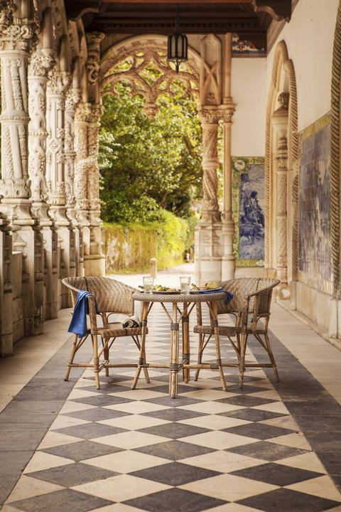 a small table and two chairs set with drinks and food on a hotel terrace in portugal with black and white tile floors and decorative columns