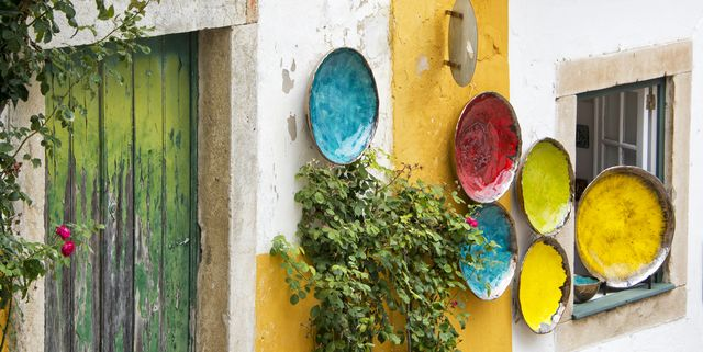 colorful plates hanging on a wall in obidos portugal