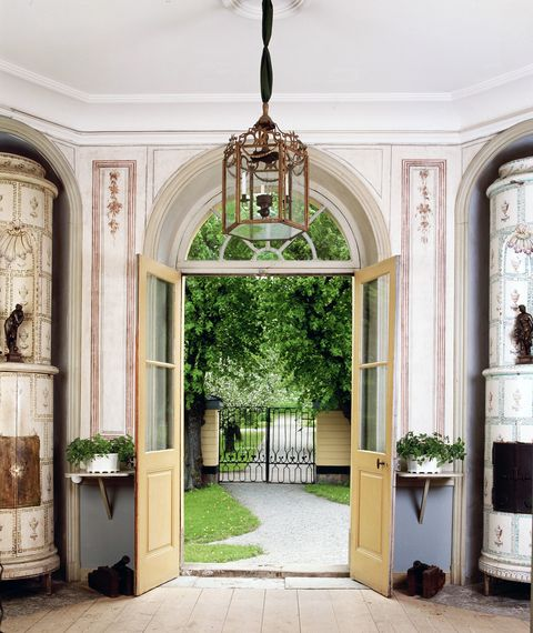 a welcomeing entry with a large chandelier framed by yellow french doors hat are open to the sidewalk and lawn