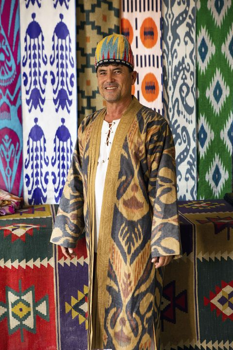 a colorful backdrop of ikat fabrics with a man in an ikat robe posed in front