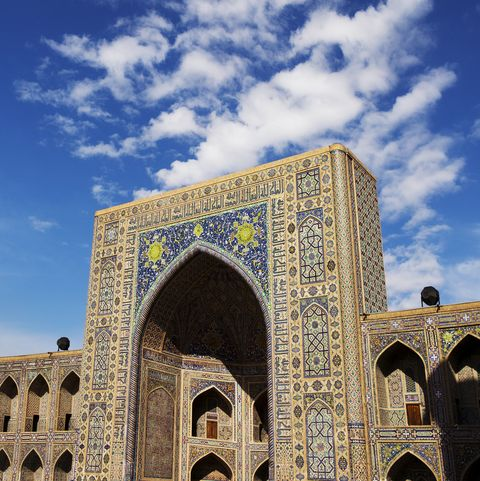 a blue and tan colored exterior of a building with intricate tilework against a vivid blue sky