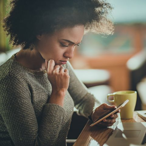 Worried African American woman using cell phone while working at home.