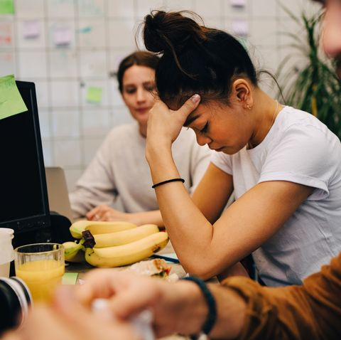 Worried businesswoman sitting amidst colleagues at desk in creative office