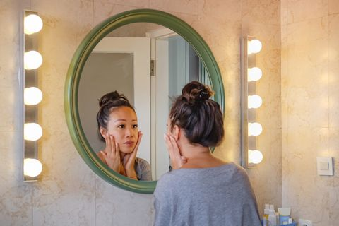 worried east asian woman checking her face skin in the mirror