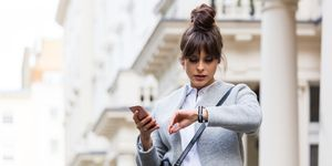 Worried woman standing with smart phone in front of city house