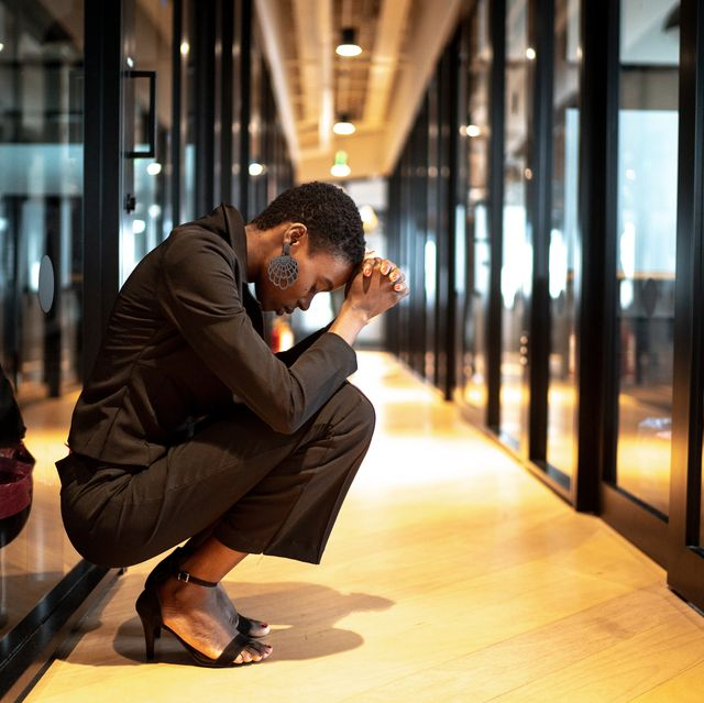 Worried young businesswoman at corridor office