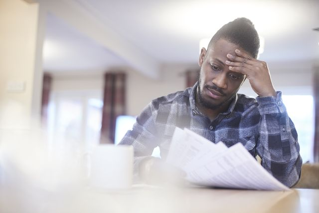 worried young male reading through household bills