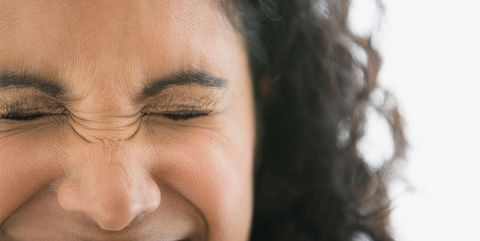 Woman wrinkling nose and forehead laughing