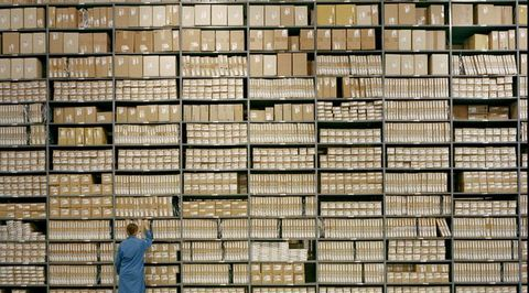 20 - 30 year old female worker pulls box off of warehouse shelf