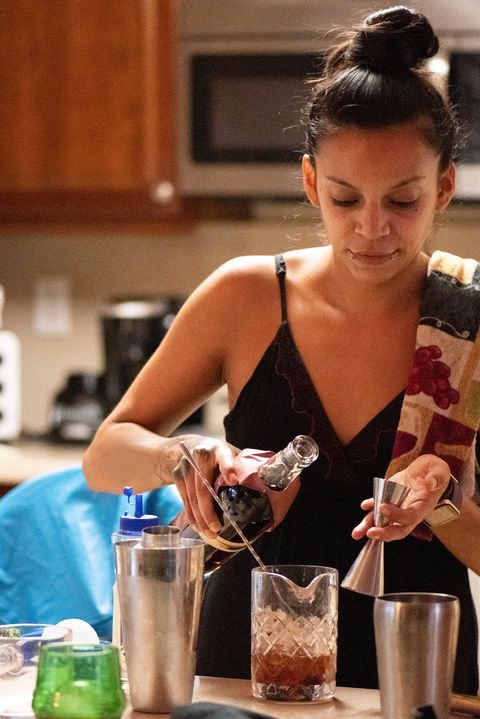 30 year old hispanic woman bartender making drinks at home in florida usa