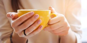 Yellow mug in the hands of a young woman. Girl holding a Cup of coffee in a cafe. Coffee break, Breakfast. The concept of power. Close up.