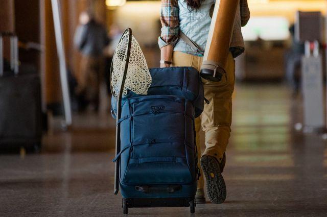a person wheeling a yeti suitcase through an airport