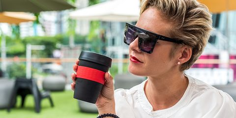Businesswoman sitting in the garden during day holding reusable coffee cup